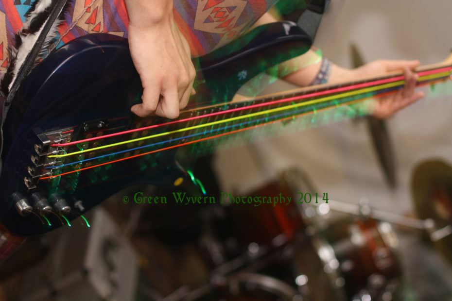 Bass guitar with multicoloured strings blurred by movement