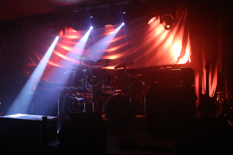 Stage with drumkit, lit by lights.